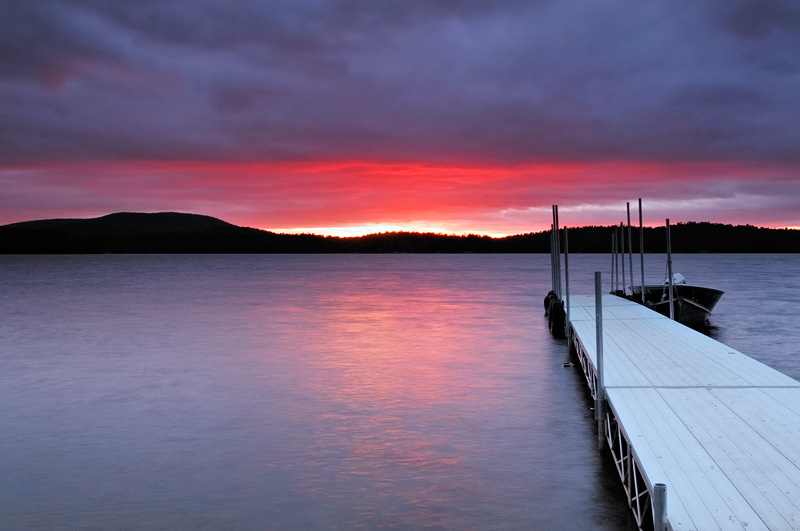 Stormy sunset and Red Top Inn boat dock at Tupper Lake New York